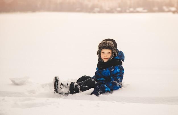Мальчик зимой сидит на снегу. игры на улице