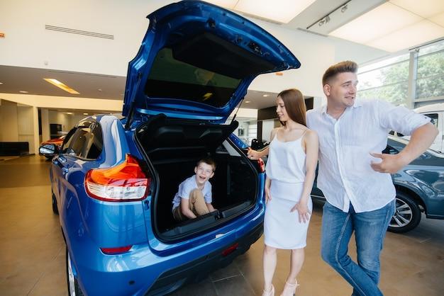 両親が新しい車を選ぶ間、小さな男の子がトランクに座っています。