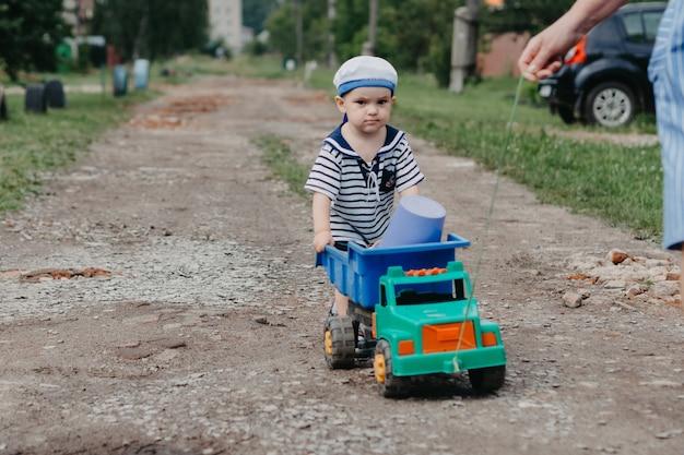 어린 소년이 미소를 짓고 바깥 끈에 장난감 자동차를 운전합니다.