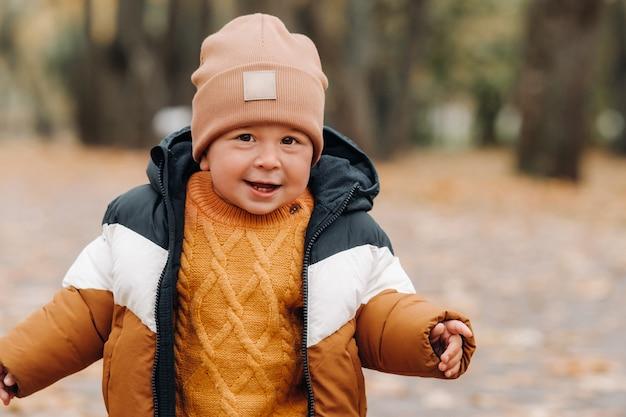 秋の公園で小さな男の子が微笑む