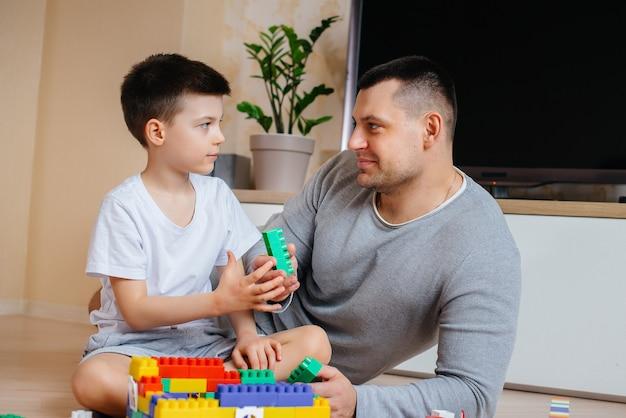 小さな男の子が父親と一緒にコンストラクターに演じられ、家を建てます。家族の家の建設。