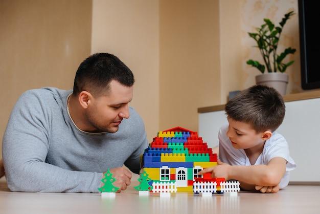 Маленький мальчик вместе с отцом играет конструктора и строит дом. строительство семейного дома.