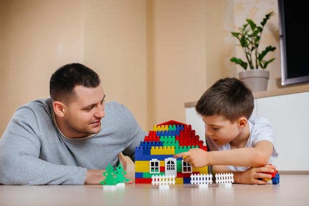 아버지와 함께 어린 소년은 건설자가 연기하고 집을 짓습니다. 가족 주택 건설.