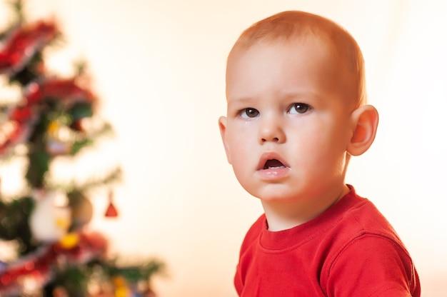 サンタクロースからの贈り物を待っている小さな男の子は、新年のツリーの近くで悲しくて泣いています。