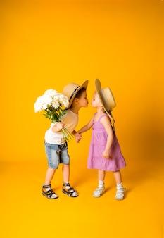花の花束を持った小さな男の子が、テキスト用のスペースのある黄色い表面の麦わら帽子をかぶった小さな女の子にキスします。