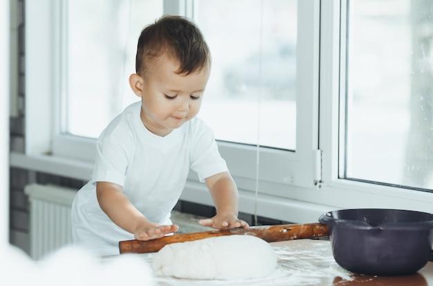 Маленький мальчик со скалкой на кухне готовит выпечку теста