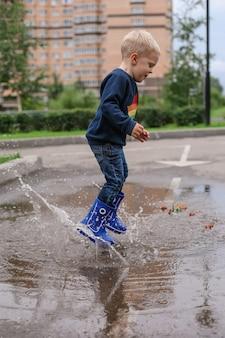 青いゴム長靴で金髪の小さな男の子が水たまりに飛び込む