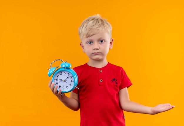 黄色の壁を見ながら青い目覚まし時計を保持している赤いtシャツを着ているブロンドの髪と青い目を持つ少年