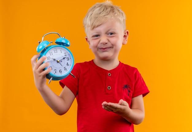 黄色の壁を見ながら青い目覚まし時計を示す赤いtシャツを着ているブロンドの髪と青い目を持つ小さな男の子