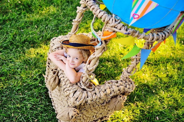 Маленький мальчик с вьющимися волосами в соломенной шляпе, сидящий в корзине с синим воздушным шаром, улыбается на фоне травы и готовится к полету.
