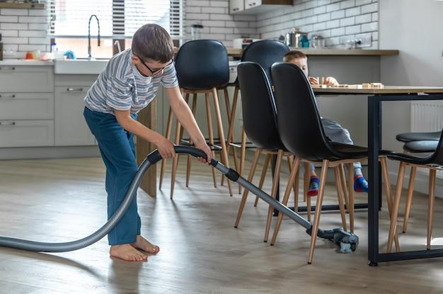 안경을 든 어린 소년이 진공 청소기로 집을 청소합니다.