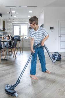 Маленький мальчик в очках убирает дом пылесосом.