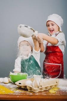Маленький мальчик со своей сестрой готовит обед
