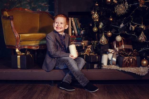 Маленький мальчик с рыжими волосами и веснушками на темном фоне. золотой и черный. елка и новогодние украшения