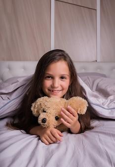 パジャマ姿の小さなブルネットの少女は、テディベアと一緒にベッドの上のベッドリネンの上に横たわっています