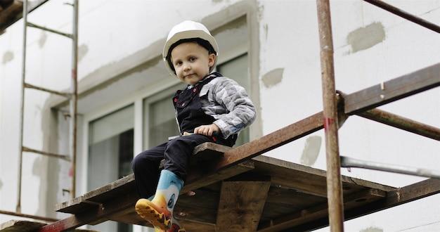 白いヘルメットをかぶった小さなビルダーが足場に座っています幸せな小さな男の子が足をぶら下げています