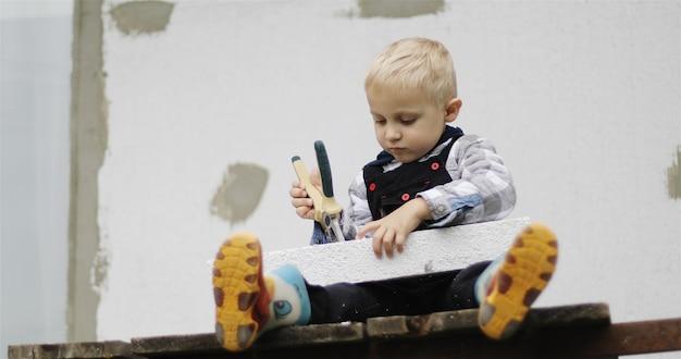 白いヘルメットをかぶった小さなビルダーが、ペンチを手に持って足場に座っています。