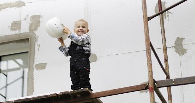 白いヘルメットをかぶった小さなビルダーが足場の上に立って帽子を調整します