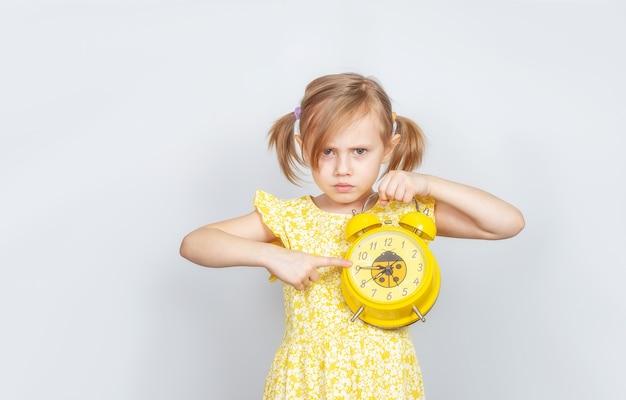 어린 백인 소녀는 그녀의 손에 알람 시계를 보유하고 카메라를 화가 나서 시계에 손가락을 가리 킵니다.