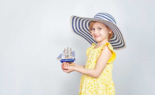Маленькая кавказская девочка в широкополой шляпе держит в руках игрушечную лодку. концепция летнего отдыха