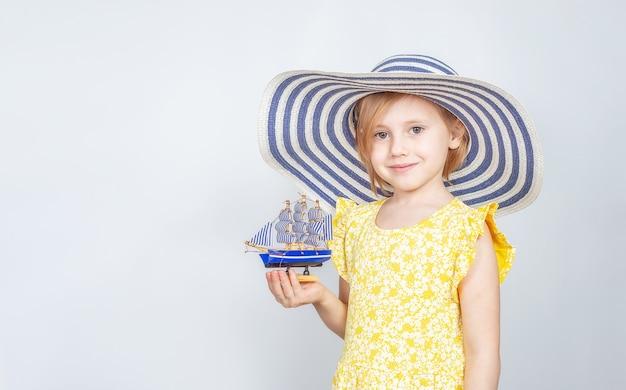 챙이 넓은 모자에있는 어린 백인 소녀는 그녀의 손에 장난감 보트를 보유하고 있습니다. 여름 휴가의 개념