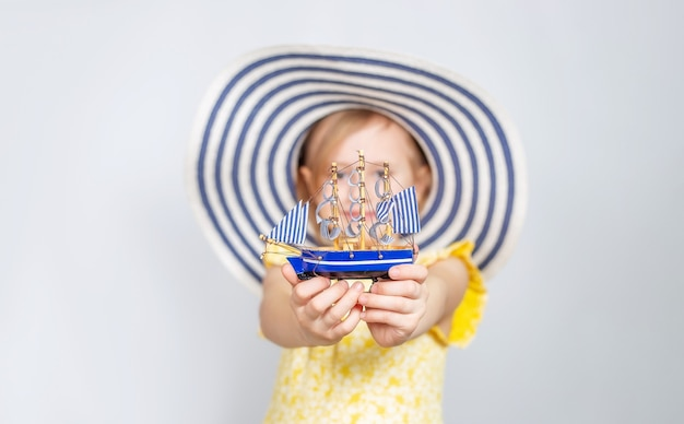 챙이 넓은 모자에있는 어린 백인 소녀는 앞으로 장난감 보트를 보유하고 있습니다.
