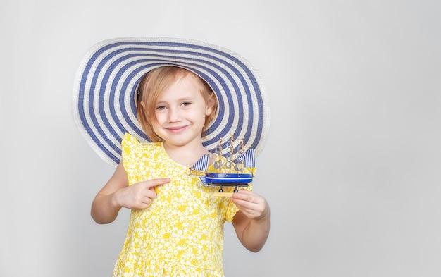챙이 넓은 모자를 쓴 작은 백인이 장난감 보트를 가리키고있다. 여름 휴가의 개념