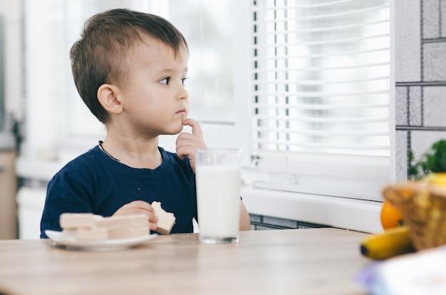 小さな魅力的な男の子がキッチンでワッフルを食べ、ミルクを飲みます