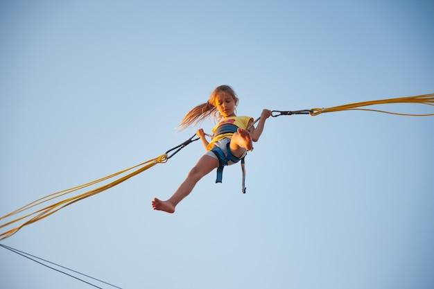陽気な女の子が弾力のある明るい輪ゴムで飛んで、暖かい太陽の下で待望の休暇を楽しんでトランポリンにジャンプします