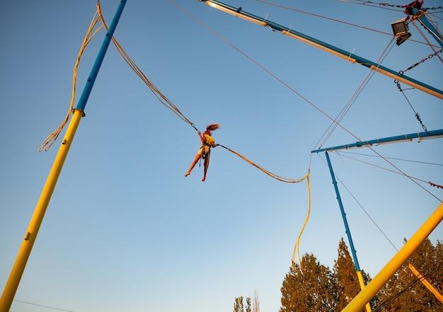 Маленькая жизнерадостная девочка летает на пружинящих ярких резинках и прыгает на батуте, наслаждаясь долгожданным отдыхом под теплым солнышком.