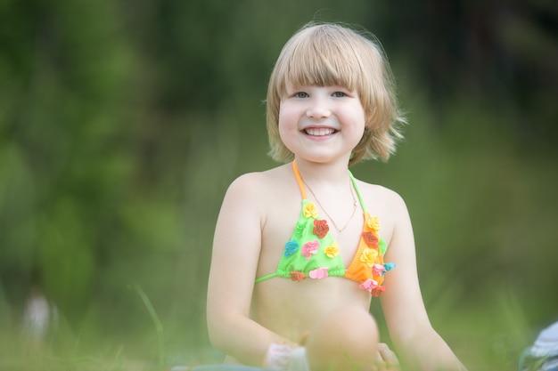暖かい夏の日に緑の芝生の上で明るい水着を着た小さな陽気な女の子。