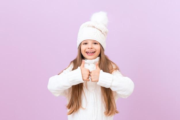 겨울 따뜻한 모자를 쓴 쾌활한 소녀가 엄지손가락을 치켜들고 있습니다.