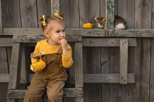 陽気な女の子が木製のはしごに座ってトウモロコシを食べます。子猫は子供の隣に座っています。