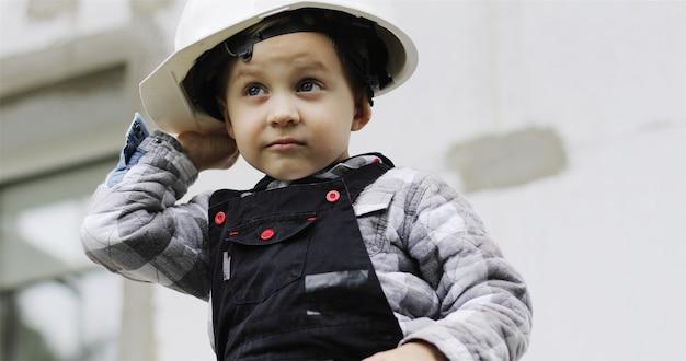 白いヘルメットの小さな子供ビルダーが足場の男の子の肖像画に座っています