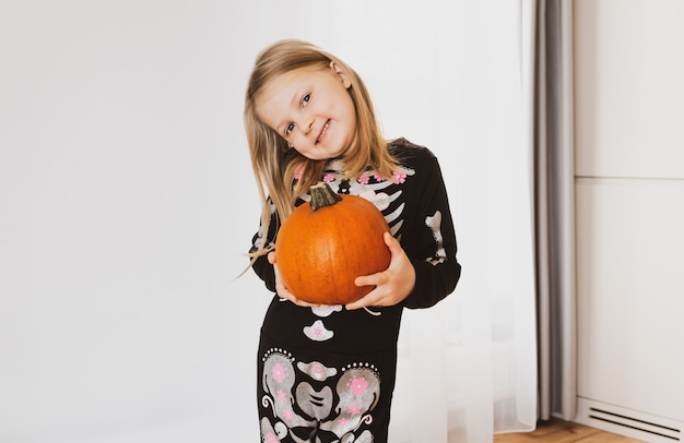 Маленькая девочка в костюме хэллоуина улыбается и держит в руках тыкву.