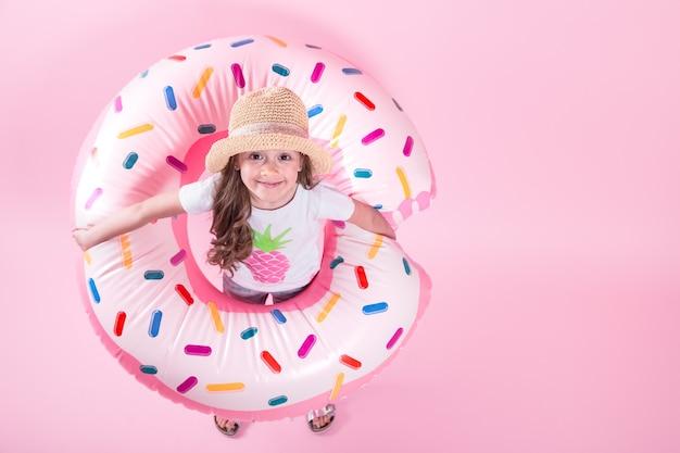ドーナツインフレータブルサークルの上に横たわるカジュアルな服装で小さな子供女の子。ピンクの背景。上面図。夏のコンセプトです。