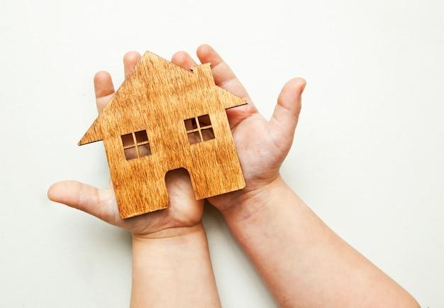 小さな子供は彼の手で木製の平らな家を保持しています。