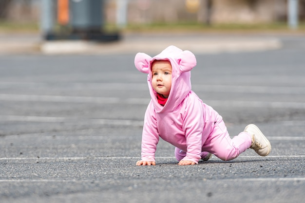 자동차 주차장에서 아스팔트에 크롤링 핑크 드레스에 어린 아이
