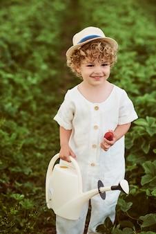 Маленький кудрявый мальчик в белой шляпе и льняной одежде в поле