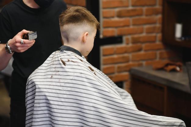 小さなかわいい男の子がスタイリストの美容院に座って、小学生が美容院でヘアカットをしている、理髪店の子供、短い男性のヘアカット。