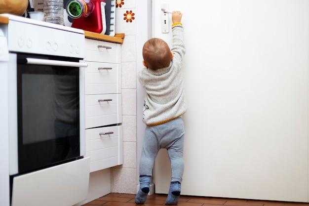 귀여운 소년이 방의 문을 열고 싶어합니다. 그의 손으로 부엌에서 문 손잡이에 도달하려고 아기의 초상화. 어린이 보안.