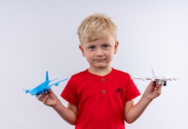 흰 벽을 보면서 파란색과 흰색 장난감 비행기를 비행하는 빨간 티셔츠를 입고 금발 머리와 파란 눈을 가진 작은 귀여운 소년