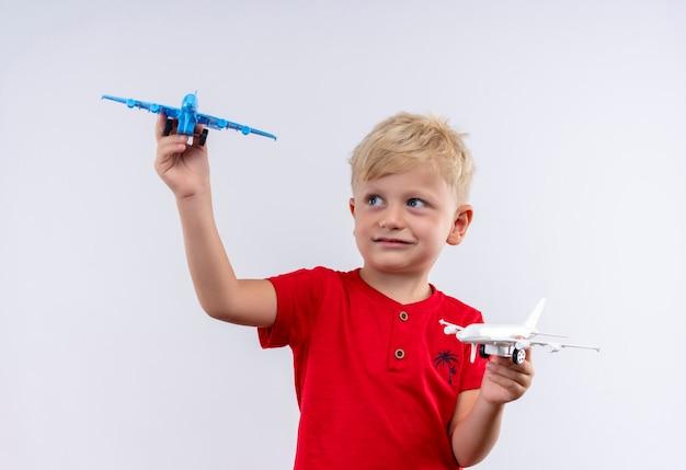 Маленький милый мальчик со светлыми волосами и голубыми глазами в красной футболке, летящий на бело-голубом игрушечном самолетике, глядя на белую стену