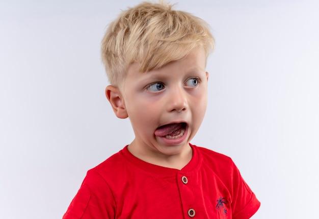 Маленький милый мальчик со светлыми волосами и голубыми глазами в красной футболке смотрит сбоку, показывая язык на белой стене