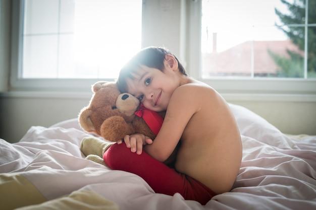 ベッドにテディベアが付いている少しかわいい少年