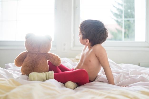 Маленький милый ребенок с плюшевым мишкой на кровати