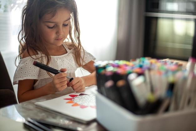 Маленькая милая девочка рисует в альбоме круговой узор мандалы арт-маркерами