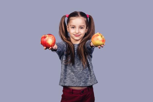 かわいい女の子が2つのリンゴを手に持って、あなたに提供します。健康的な食事の概念。灰色の表面に分離