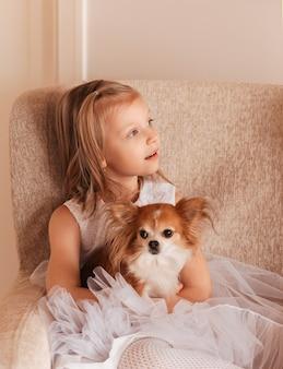 美しい白いドレスを着た小さなかわいい女の子は、小さな犬のチワワを保持しています