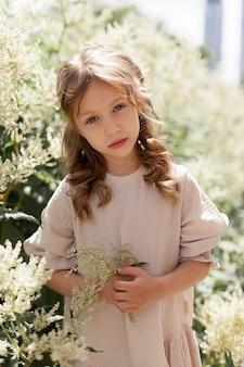 여름날 거리에서 베이지색 드레스를 입은 귀여운 소녀가 꽃을 배경으로 공원에서 손에 꽃을 들고 있습니다. 아기는 카메라를 보고 슬퍼합니다. 신선한 공기 속에서 산책.